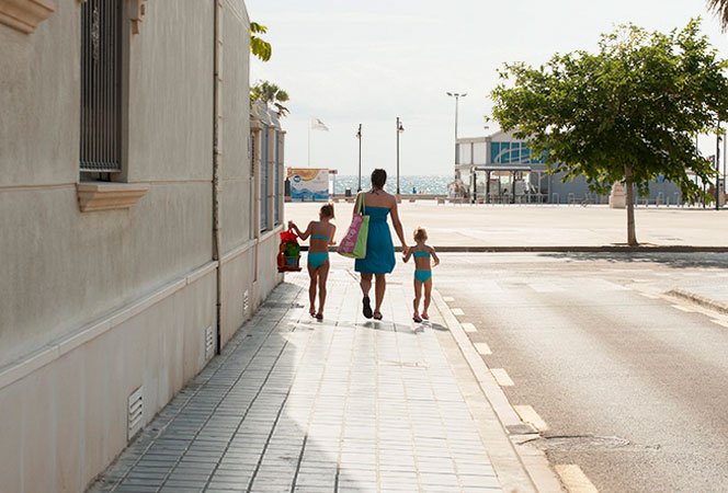 Vecinos de la Malva-rosa se dirigen a la playa por la calle Vicent de la Roda. Foto: Juanjo Hernández
